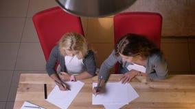 Vue supérieure de plan rapproché de la petite jolie fille blonde apprenant comment dessiner tandis que mère lui donnant une leçon banque de vidéos