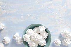 Vue supérieure de plat bleu complètement des meringues croustillantes sur la table lumineuse Copiez le For Your Information de l' images stock
