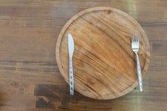 Vue supérieure de plat en bois avec le couteau et de fourchette sur en bois Photos libres de droits
