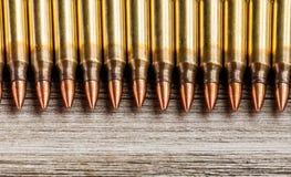 Vue supérieure de pleines balles de veste en métal de fusil dans une rangée sur le fond en bois avec l'espace de copie Photo stock