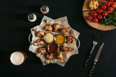 vue supérieure de poulet rôti délicieux avec des diverses sauces sur le papier, les épices, le verre de bière et les légumes de c photos libres de droits