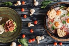 vue supérieure de prosciutto délicieux, d'oeufs au plat et de légumes frais photos stock