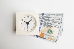 Vue supérieure de réveil blanc carré sur l'argent liquide d'argent du dollar Photo stock