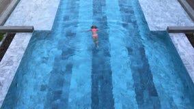 Vue supérieure de repos sain de la natation de jeune femme dans la piscine banque de vidéos