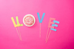 Vue supérieure de signe d'amour faite à partir des lettres et du lustre de crème sur le beignet Image libre de droits