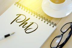 Vue supérieure de stylo, de lunettes de soleil, d'une tasse de café et du carnet écrit avec le doctorat sur le fond en bois photographie stock