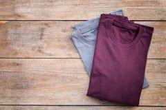 Vue supérieure de T-shirt de couleur sur la planche en bois grise images stock