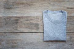 Vue supérieure de T-shirt de couleur sur la planche en bois grise image stock