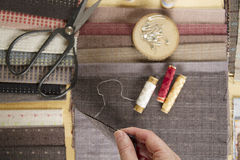 Vue supérieure de table de couture avec des tissus, des approvisionnements pour le décor à la maison ou projet et main piquants d Photographie stock