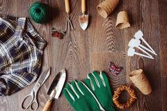 Vue supérieure de table de jardinier de ressort avec des outils, des gants, des pots de tourbe et des labels de jardin Photo libre de droits