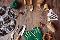 Vue supérieure de table de jardinier de ressort avec des outils, des gants, des pots de tourbe et des labels de jardin Photos stock