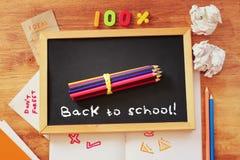 Vue supérieure de tableau noir avec l'expression de nouveau à l'école, à la pile de crayons et au papier chiffonné Images stock