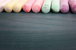 Vue supérieure de tableau noir vide avec les craies colorées Images stock