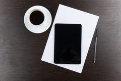 Vue supérieure de tablette avec la tasse du café et du stylo à la table Images stock