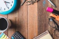 Vue supérieure de tasse de café avec l'horloge, les verres et les fournitures de bureau Image stock