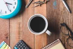 Vue supérieure de tasse de café avec l'horloge, les verres et les fournitures de bureau sur la table Photo stock