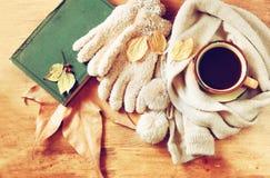 Vue supérieure de tasse de café noir avec des feuilles d'automne, une écharpe chaude et le vieux livre sur le fond en bois image  Photographie stock libre de droits
