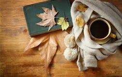 Vue supérieure de tasse de café noir avec des feuilles d'automne, une écharpe chaude et le vieux livre sur le fond en bois image  Images libres de droits