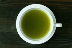 Vue supérieure de thé vert chaud vibrant de Matcha de couleur verte sur le Tableau en bois foncé de Brown images stock