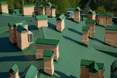 Vue supérieure de toit vert avec les cheminées oranges photographie stock