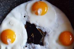 Vue supérieure de trois oeufs faisant frire sur la casserole images stock