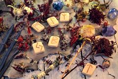 Vue supérieure de vieilles runes, de bougies vertes et de graines de fleurs d'aster sur la vieille table en bois photos libres de droits