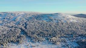 Vue supérieure de village au bas de la page de la colline en hiver longueur Petit village reculé aux collines de la colline entou banque de vidéos