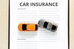 Vue supérieure de voiture de jouet d'accidents avec l'assurance auto de jouet Photographie stock libre de droits
