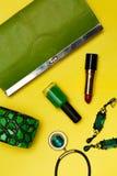Vue supérieure des accessoires de mode femelles Sac à main vert avec le collier de revenus de bracelet de rouge à lèvres Images stock