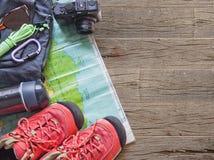 Vue supérieure des accessoires de voyage pour un voyage de montagne sur le vieux fond en bois Photos libres de droits