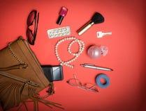 Vue supérieure des accessoires et du téléphone femelles sur un fond rouge Photos libres de droits