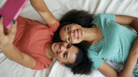 Vue supérieure des amies drôles de beau métis faisant le portrait de selfie sur le lit dans la chambre à coucher à la maison Image stock