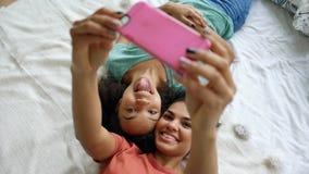 Vue supérieure des amies drôles de beau métis faisant le portrait de selfie sur le lit dans la chambre à coucher à la maison Images stock