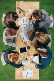 Vue supérieure des associés ayant la discussion à la table avec des documents et des dispositifs photos stock
