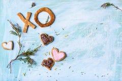 Vue supérieure des biscuits en forme de coeur, des biscuits de XO et des branches vertes avec des fleurs Image libre de droits