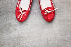 Vue supérieure des chaussures portées rouges de femme au-dessus du fond texturisé en bois filtre de style d'instagram Image libre de droits