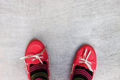 Vue supérieure des chaussures portées rouges de fille au-dessus du fond texturisé en bois Photos libres de droits