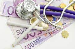 Vue supérieure des ciarettes et du stéthoscope sur l'euro argent photographie stock