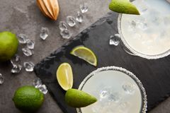 Vue supérieure des cocktails de margarita avec des morceaux de chaux, de glaçons et de presse-fruits en bois sur le dessus de tab photo stock