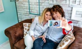 Vue supérieure des couples prenant le selfie sur un sofa Photo stock