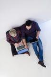 Vue supérieure des couples travaillant sur l'ordinateur portable au bureau de démarrage Photos stock