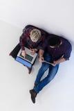 Vue supérieure des couples travaillant sur l'ordinateur portable au bureau de démarrage Photographie stock