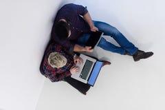 Vue supérieure des couples travaillant sur l'ordinateur portable au bureau de démarrage Image libre de droits