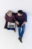 Vue supérieure des couples travaillant sur l'ordinateur portable au bureau de démarrage Images stock