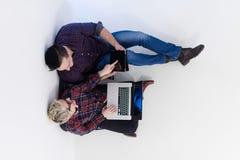Vue supérieure des couples travaillant sur l'ordinateur portable au bureau de démarrage Photo libre de droits
