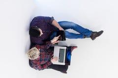 Vue supérieure des couples travaillant sur l'ordinateur portable au bureau de démarrage Photos libres de droits