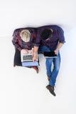 Vue supérieure des couples travaillant sur l'ordinateur portable au bureau de démarrage Image stock