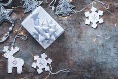 Vue supérieure des décorations de Noël, du cadeau enveloppé argenté de Noël et des décorations sur un fond en bois image libre de droits