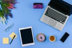 Vue supérieure des dispositifs numériques, des fleurs, de la tasse de café avec le beignet et de l'appareil-photo image stock