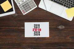 vue supérieure des dispositifs numériques, des fournitures de bureau et du calendrier 2018 photographie stock libre de droits